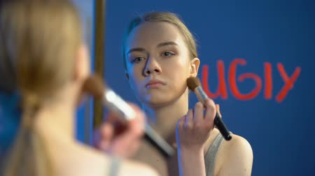 feiúra : Sad school teenager applying face powder looking mirror, word ugly written glass