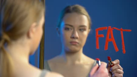 criticism : Young caucasian female writing word fat mirror glass, teenage anorexia disorder Stock Footage
