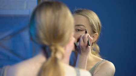 irritação : Pretty teenage female applying eyeliner front of mirror, learning to do make-up Vídeos