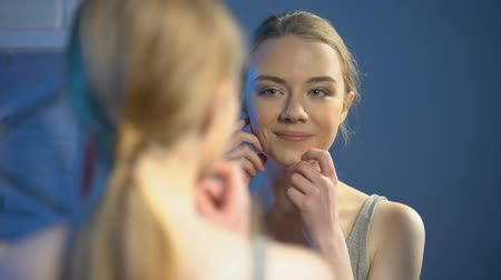 nőiesség : Happy young woman looking at mirror reflection, satisfied with skin treatment