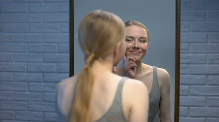 dermatologia : Young woman looking at mirror reflection and smiling in camera, natural beauty