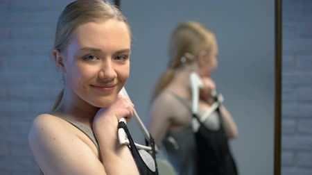 butik : Happy student trying on black dress, preparing for date, smiling on camera