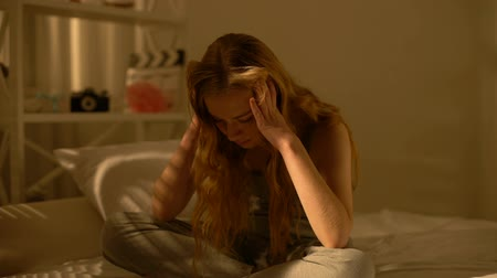 regret : Stressed female teenager sitting home bed, puberty age difficulties, depression