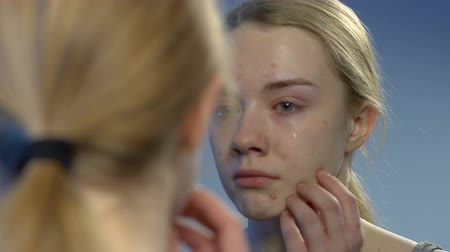 esteem : Crying young lady looking with disgust at face acne in mirror, awkward age Stock Footage