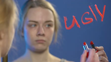 esteem : Upset teen girl writing with lipstick word ugly on mirror, low self-esteem Stock Footage