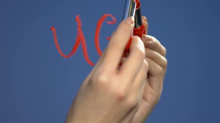 teen age : Female hand writing with lipstick ugly word on glass, self-esteem problems