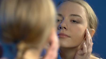 vanity : Smiling teen girl applying foundation cream, enjoying beauty, ready for date Stock Footage