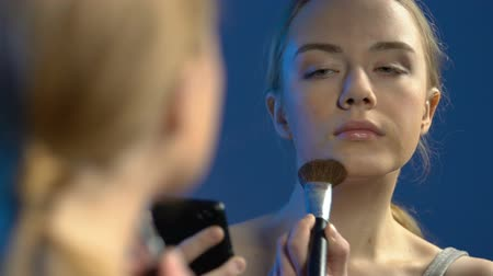 vanity : Female teenager watching make-up video lessons on smartphone, applying powder