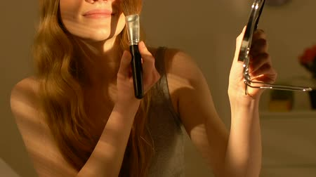 ipuçları : Young smiling girl applying skin powder, preparing for date, make-up tips Stok Video
