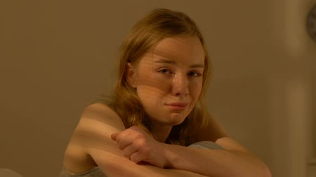 cheated : Crying teen girl sitting alone in room, helpless bullying victim violence result Stock Footage