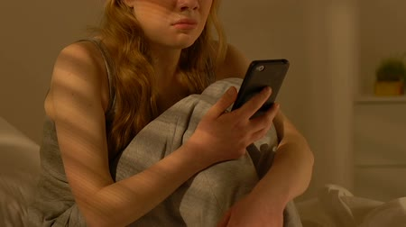 cheated : Young lady holding smartphone and crying, break up with boyfriend, relations Stock Footage