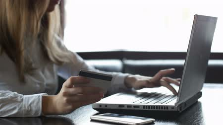 hasznosság : Young woman using laptop and credit card paying bills online, money transfer
