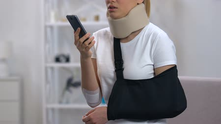 bandagem : Sad woman in arm sling and cervical collar talking phone, feeling neck pain
