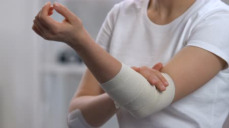 肘 : Woman wearing elastic wrap on painful elbow, arthritis problems, sickness 動画素材