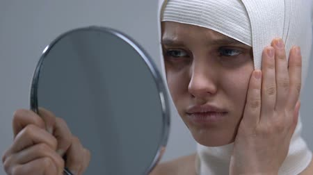 outlook : Upset woman in headwrap looking at mirror reflection, unsuccessful surgery