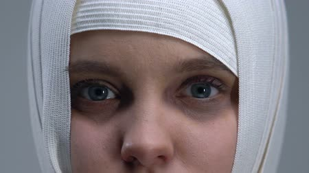 traumatic : Frightened girl in headwrap looking at camera, violence victim, close-up Stock Footage