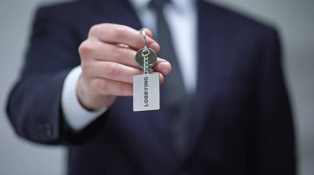 political intervention : Lobbying word on keychain in businessman hand, illegal protection of interests