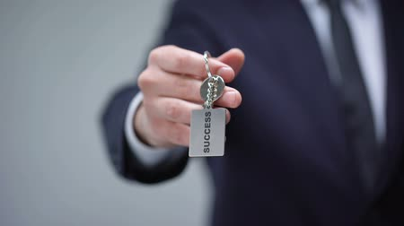self promotion : Success word on keychain in businessman hand, personal development courses Stock Footage
