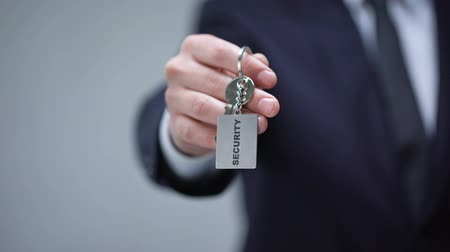 secret service : Security word on keychain in businessman hand, home safety system, guard service Stock Footage