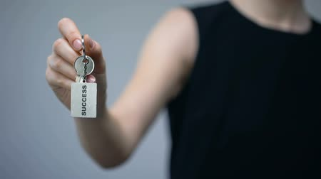 self promotion : Success inscription on keychain in woman hand, tips to attract money, prosperity Stock Footage