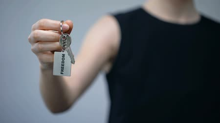 достигать : Freedom word on keychain in female hand, women rights, independent choice