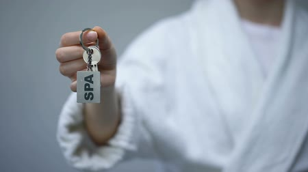 realty : Woman in bathrobe holding keys with SPA word, recreation services in hotel