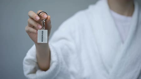 foglalás : Customer in bathrobe holding keys with Reserved word, booking hotel rooms