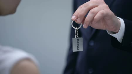 self promotion : Man giving woman keys to Success, secret tips to turn dream into reality closeup