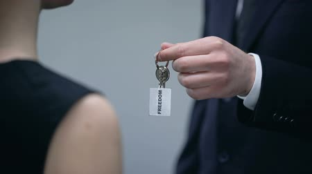 self promotion : Man in suit giving woman keys to Freedom, leadership courses, self-development Stock Footage