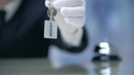 amministratore : Receptionist showing keychain with Resort word, luxury property rental, closeup