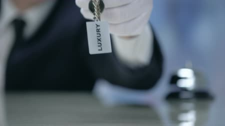 evsahibi : Luxury written on keychain in receptionist hand, premium quality hotel, closeup