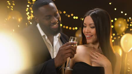 pick : Smiling afro-american male offering dancing lady glass of champagne, flirt Stock Footage