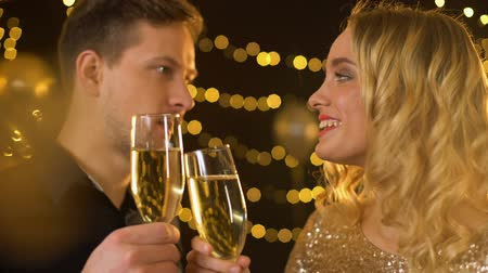 şarap kadehi : Young male and female looking each other clinking glasses, festive atmosphere