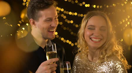şarap : Celebrating young couple toasting drinking champagne, festive lights background Stok Video