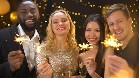 bengália : Carefree friends enjoying new year celebration in night club, holding sparklers Stock mozgókép