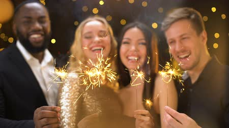 друзья : Cheerful friends showing sparklers shaped 2020, having fun in night club, event
