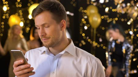 ano novo : Male chatting social networks app on smartphone, feeling bored glamorous event Stock Footage