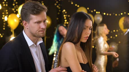 jealous : Upset woman ignoring apologizing boyfriend at holiday party, misunderstanding
