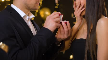 ring : Young man presenting diamond ring to girlfriend, proposing at party, marriage