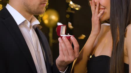 propor : Excited young woman looking at gold ring presented by man, marriage proposal