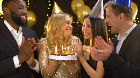 tebrik etmek : Happy blond female blowing cake candles, friends congratulating woman birthday