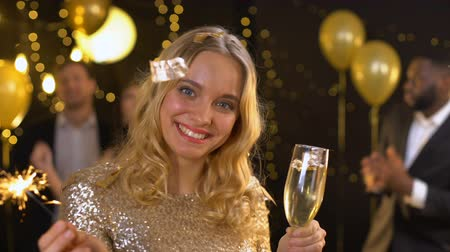 convidado : Happy young lady with glass of champagne holding sparkler, new year celebration Vídeos