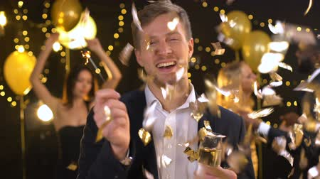 csillagszóró : Cheerful drunk man enjoying celebration, holding sparkler and champagne glass