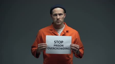 заключенный : Prisoner holding Stop prison overcrowding sign in cell, life conditions in jails