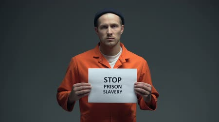 penas : Prisoner holding Stop prison slavery sign, human rights protection, violence