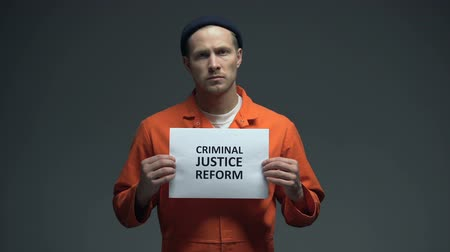 dishonesty : Male prisoner holding Criminal justice reform sign, human rights protection