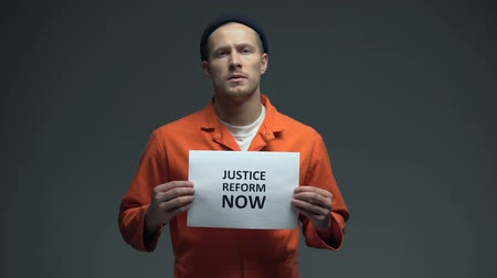наказание : Caucasian prisoner holding Justice reform now sign, human rights protection Стоковые видеозаписи