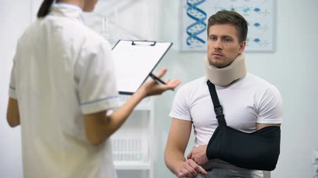 手首 : Doctor writing diagnosis to upset patient in foam cervical collar and arm sling