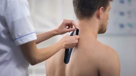osteopata : Experienced doctor applying Y-shaped tapes on patient upper back, healthcare