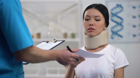 health insurance : Male doctor giving bill to shocked patient in foam collar, expensive medicine